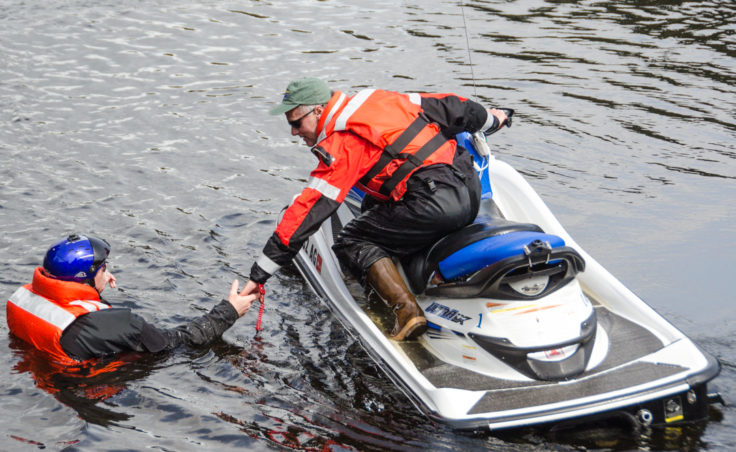 CBJ Park Ranger Dale Gosnell reaches for Mike Folkerts during a training exercise at Auke Lake (Photo by Heather Bryant/KTOO)