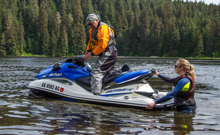Stu Robards prepares to head out to the middle of the lake to practice fast turning as Lizzie Solger pushes him off. Solger is the president of the Juneau Personal Watercraft Club. (Photo by Heather Bryant/KTOO)