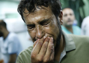 A Palestinian man cries after bringing a child, wounded in a strike on a compound housing a U.N. school in Beit Hanoun, in the northern Gaza Strip, to the emergency room of the Kamal Adwan hospital in Beit Lahiya on Thursday. Lefteris Pitarakis/AP