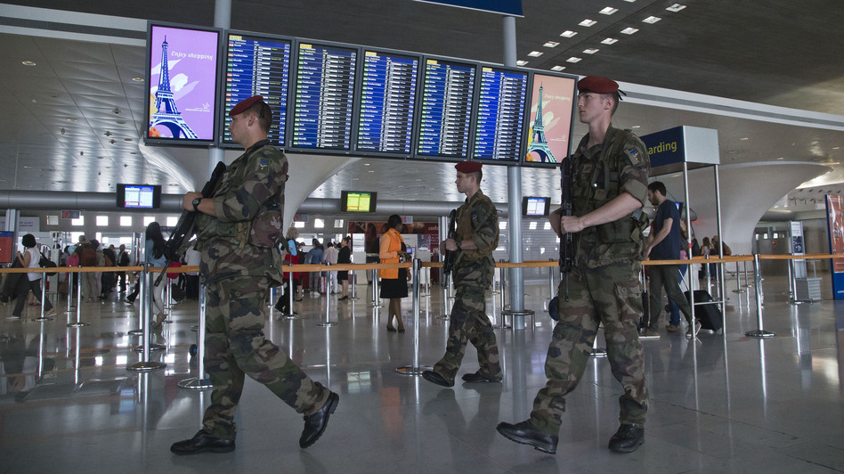In Paris, soldiers patrol at Charles de Gaulle airport last week. French airports have reportedly agreed to a new TSA policy requiring electronic devices to be powered up before they're allowed on U.S.-bound flights. Michel Euler/AP