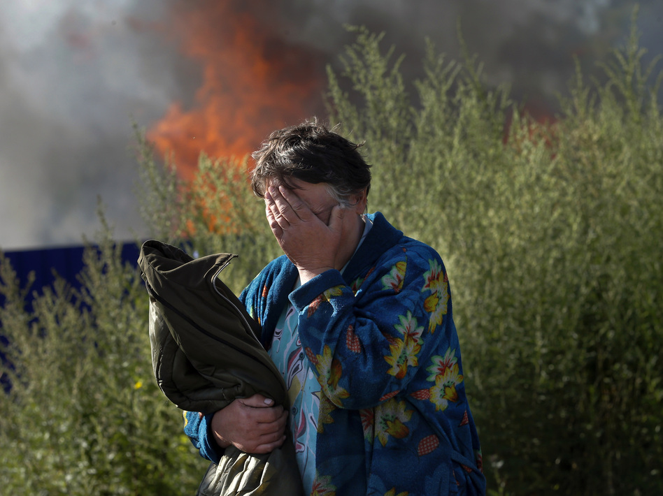 A woman cries near her burning house after shelling in the city of Slovyansk, Donetsk Region, eastern Ukraine, last month. The city of 100,000 has now been retaken from pro-Russian separatists. Dmitry Lovetsky/AP