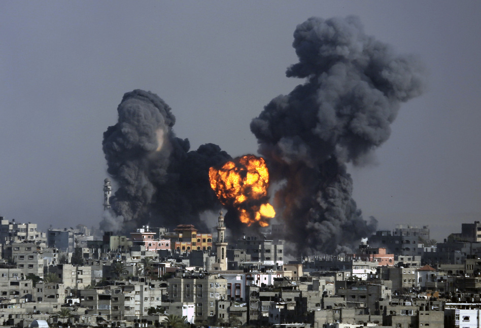 Smoke and fire from the explosion of an Israeli strike rise over Gaza City on Tuesday. Israeli airstrikes pummeled a wide range of locations along the coastal area as diplomatic efforts intensified to end the two-week war. Hatem Moussa/AP