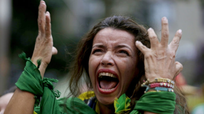A fan screams as she watches Brazil lose to Germany, in a live telecast in Belo Horizonte, Brazil, Tuesday. The host nation is reeling from its loss in the World Cup semifinal. Bruno Magalhaes/AP