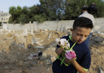 Palestinian Saeb Afana, 12, stands on the edge of a large crater from an Israeli missile strike that destroyed several graves, as he carries flowers at a cemetery in Gaza City on Monday. Lefteris Pitarakis/AP
