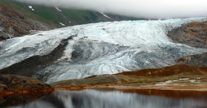 A glacier reflects in a naturally occurring pool of rusty, acidic water at the site of one of the KSM Prospect's planned open-pit mines. (Ed Schoenfeld/CoastAlaska News)