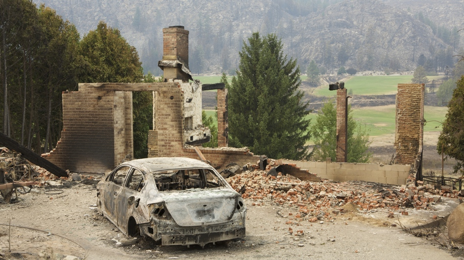 A burned-out car sits in front of a ruined house in this photo taken Sunday near Pateros, Wash. Large fires have destroyed hundreds of homes in the state this month. Stephen Brashear/Getty Images