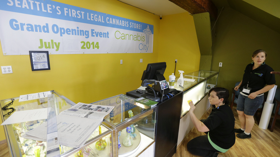 Amber McGowan, left, and Krystal Klacsan work Monday at Cannabis City in Seattle, a day before the store is to begin legal pot sales on Tuesday. The store will be for now the only one in Seattle to sell recreational marijuana. Ted S. Warren/AP