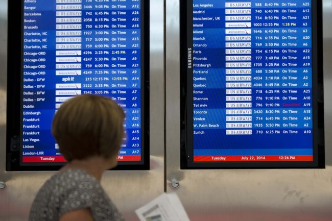 A woman passes by a departure board at Philadelphia International Airport showing that US Airways Flight 796 to Tel Aviv has been canceled Tuesday. Matt Rourke/AP