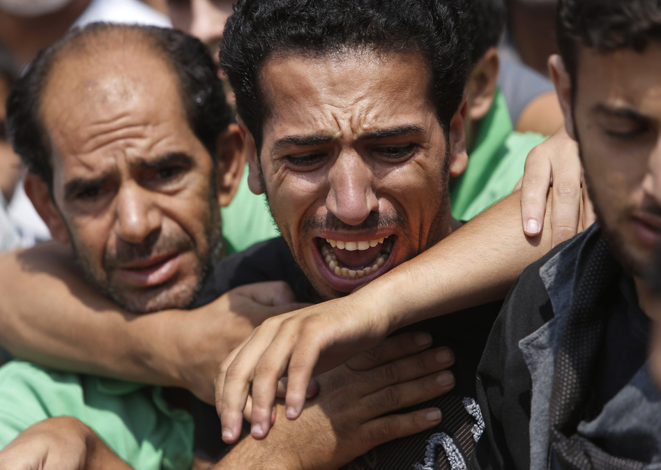 A relative bursts into tears in front of the bodies of seven members of the Kelani family, killed overnight by an Israeli strike in Gaza City. Lefteris Pitarakis/AP