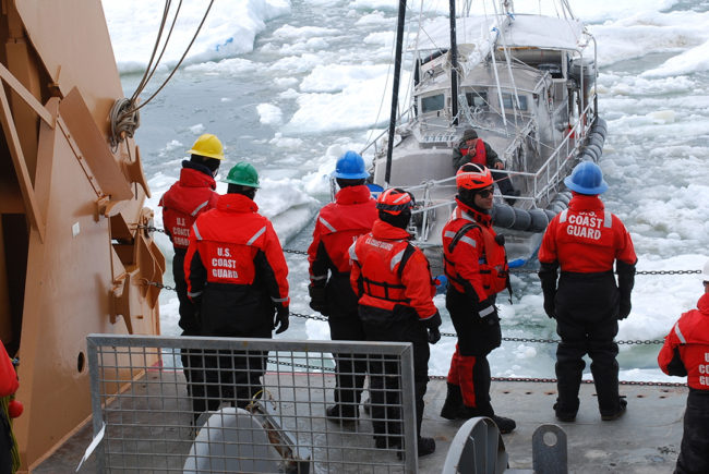 Coast Guard Cutter Healy crewmembers make contact with a mariner aboard his 36-foot sailboat trapped in Arctic ice approximately 40 miles northeast of Barrow, Alaska, July 12, 2014. Coast Guard 17th District watchstanders in Juneau were contacted by North Slope Borough Search and Rescue that a man, sailing his sailboat from Vancouver, Canada, to eastern Canada via the Northwest Passage, needed assistance after his vessel had become trapped in the ice. (Photo courtesy of Coast Guard Cutter Healy)