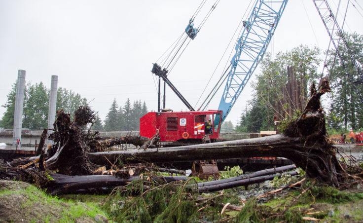 The crane at Brotherhood Bridge removed logs from the river yesterday after a log jam formed at the bridge. (Photo by Heather Bryant/KTOO)