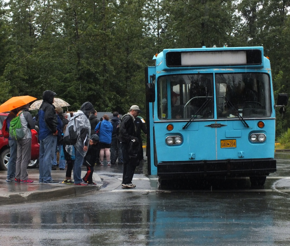 Passengers board a bus at the Mendenhall Glacier Visitor Center on Tuesday. (Photo by Matt Miller/KTOO)