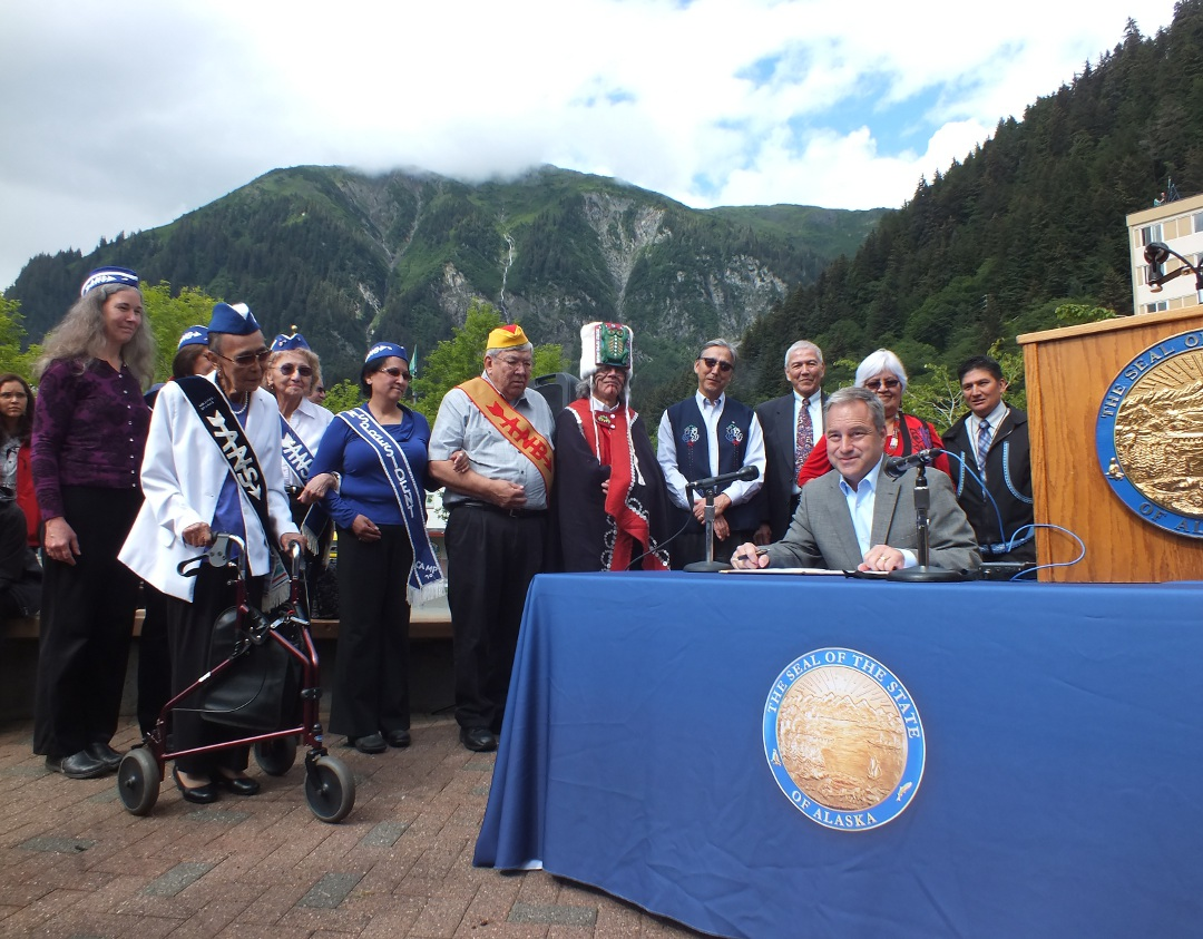 Surrounded by the late Tlingit elder's family and friends, Gov. Sean Parnell signs legislation establishing Nov. 14 as Dr. Walter Soboleff Day in Alaska. (Photo by Casey Kelly/KTOO)