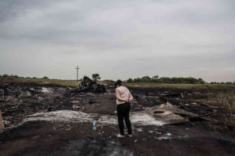 A woman looks at the wreckage of Malaysia Airlines Flight MH17 in Grabovka, Ukraine, on Friday. One day after the downing of the jetliner over eastern Ukraine, investigators are trying to learn more about the crash and who might be responsible. The passenger jet had nearly 300 people on board; none survived. Brendan Hoffman/Getty Images