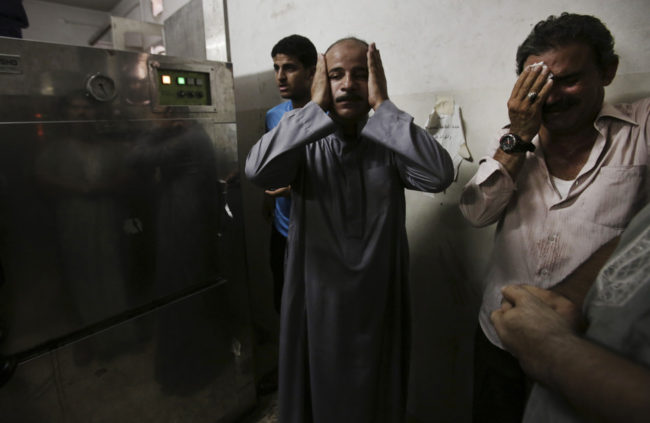 In the morgue of Gaza's Shifa hospital, Palestinian relatives mourn following an explosion that reportedly killed at least 10 people Monday, nine of them said to be children. Adel Hana/AP