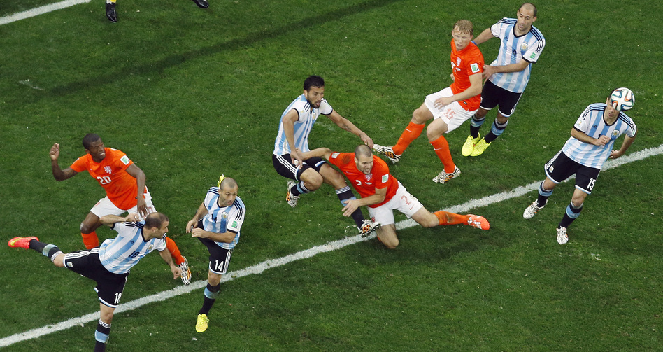 Players go for the ball during the World Cup semifinal soccer match between the Netherlands and Argentina at the Itaquerao Stadium in Sao Paulo, Brazil, on Wednesday. Fabrizio Bensch/AP