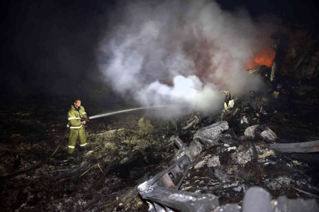 A firefighter sprays water to extinguish a fire amid the wreckage from the Malaysian airliner crash in eastern Ukraine on Thursday. A Malaysia Airlines Boeing 777 with 295 passengers and crew aboard crashed near the Donetsk area of Ukraine that has been wracked by a separatist insurgency. Alexander Khudoteply/AFP/Getty Images