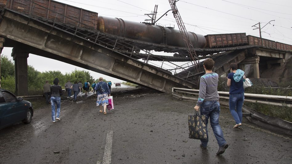 People walk under a destroyed railroad bridge over a main road leading into the city of Donetsk in eastern Ukraine Monday. Kiev is calling on pro-Russian militants to disarm before holding peace talks. Dmitry Lovetsky/AP
