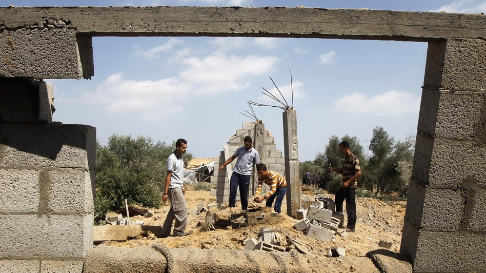 Palestinians inspect a damaged building after an Israeli air strike in Khan Yunis in the southern Gaza Strip on Sunday. Said Khatib/AFP/Getty Images