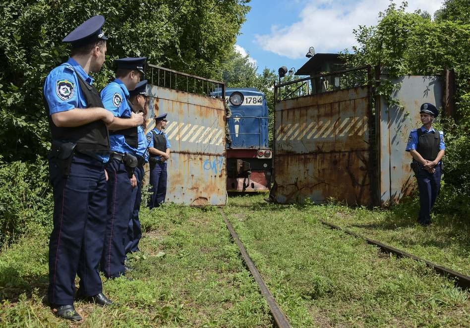 Police officers secure a refrigerated train loaded with bodies of the passengers of Malaysian Airlines flight MH17 as it arrives in a Kharkiv factory on Tuesday. Olga Ivashchenko/AP