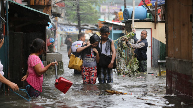 Residents wade through floods as they go back to their home while Typhoon Rammasun batters suburban Quezon city, north of Manila, on Wednesday. Aaron Favila/AP