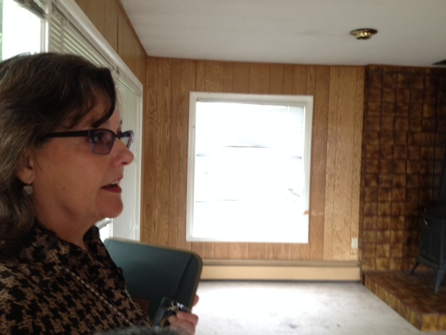 Jill Reese talks about the project inside one of the homes slated for removal. (Photo by Hillman/KSKA)