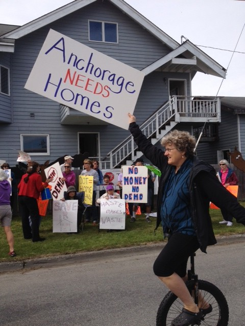 Residents protest in front of a home slated for removal for the proposed Knik Arm Bridge. (Photo by Anne Hillman/KSKA)