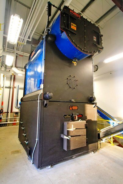 This biomass-fueled boiler at Tok School burns chipped timber waste to generate heat and electricity for the campus. ( KUAC file photo)