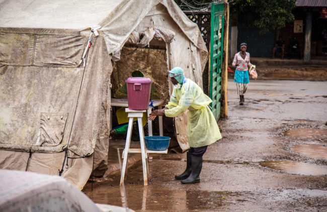 A health worker cleans his hands with chlorinated water before entering a Ebola screening tent, at a government hospital in Kenema, Sierra Leone, Monday. The World Health Organization cites 1,848 cases of the deadly disease across West Africa. Michael Duff/AP