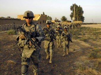 U.S. Army soldiers from 1st Platoon, G Troop, Task Force 1-35, 2nd Brigade Combat Team, move out on patrol in Iraq in 2008. A bipartisan panel says a Pentagon plan to cut Army strength go too far. Sgt. Eric C. Hein/AP