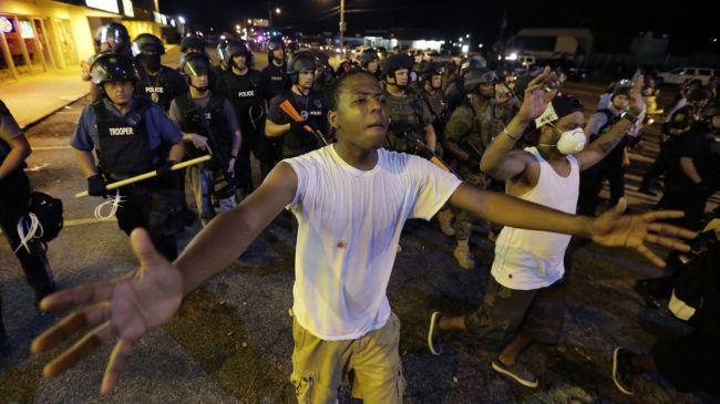 Protesters walk in front of a line of police as authorities try to disperse a demonstration in Ferguson, Mo. early Wednesday. The St. Louis suburb saw less violence than recent nights of protests. Charlie Riedel/AP