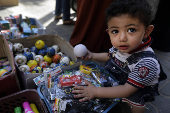 A Palestinian child goes through toys Wednesday at a vendor's stall in a market in Gaza City. Lefteris Pitarakis/AP