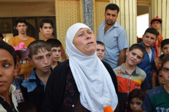 Displaced Iraqis wait for aid Friday at a mosque on the outskirts of Irbil in northern Iraq.AP