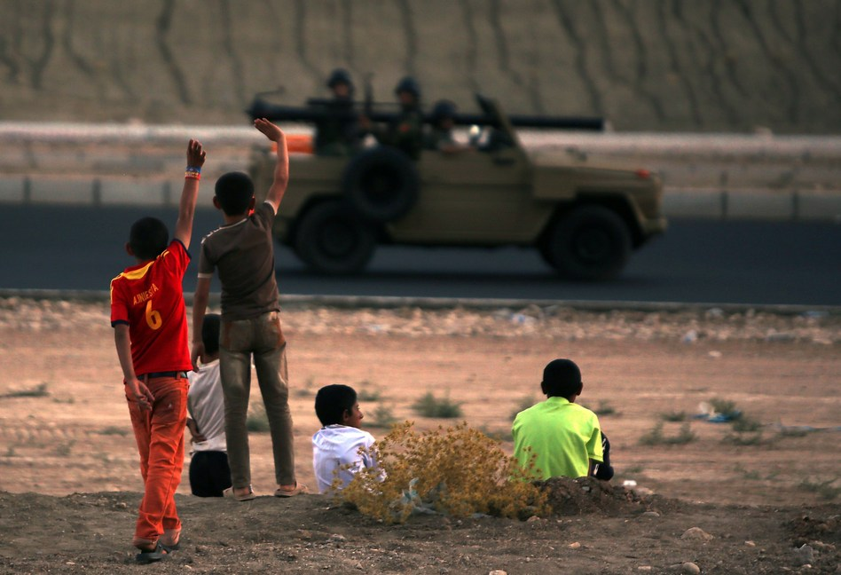Iraqi children from the Yazidi community wave to Kurdish peshmerga forces near Dohuk, the Kurdish region of autonomous Kurdistan in Iraq. The children fled with their families from their hometown, which was attacked by Sunni militants from the Islamic State. Ahmad Al-Rubaye/AFP/Getty Images