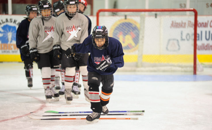 Sunny Monset participates in a drill consisting of stepping over evenly spaced hockey sticks then break into a sprint.