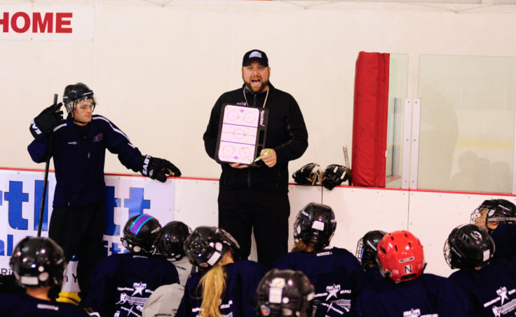 Rocky Mountain Hockey School coach Zac Desjardins draws up drill while players look on.