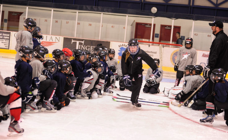 Emma Kaelke demonstrates a drill as young players look on during a Rocky Mountain Hockey School session at Treadwell Ice Arena.