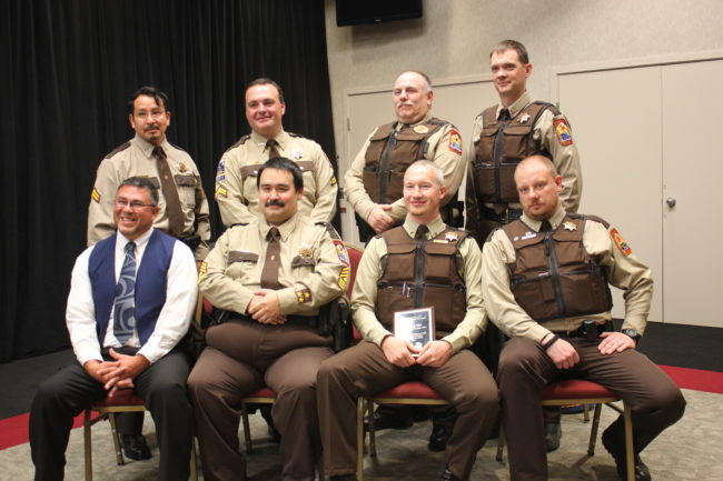 Tlingit-Haida Central Council's VPSO coordinator Jason Wilson (bottom row, left) sits with the seven VPSOs serving Southeast Alaska after a ceremony held in Juneau Monday. VPSO of the Year Zach West holds his award. (Photo by Lisa Phu/KTOO)