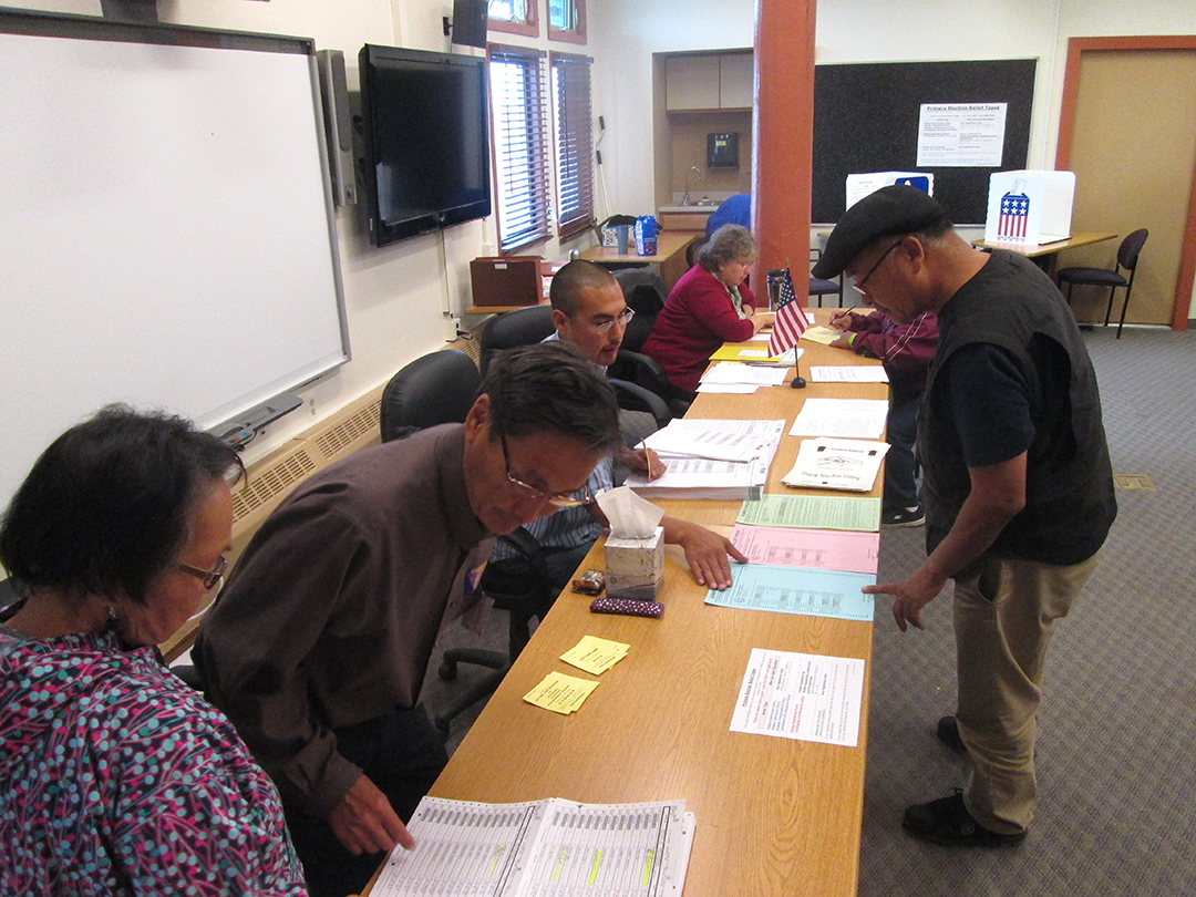 Voters at the Lower Kuskokwim School District choosing primary election ballots on Tuesday, August 19th, 2014. Some voters had to ask for assistance understanding the ballot translation.(Photo by Daysha Eaton/KYUK)