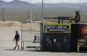 A man closes off an entrance to the Last Stop shooting range in White Hills, Ariz., on Wednesday. Instructor Charles Vacca was killed at the range Monday by a 9-year-old girl he was teaching to use an Uzi submachine gun. John Locher/AP