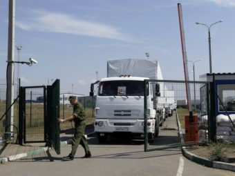 A Russian border guard opens a gate into the Ukraine for the first trucks from the Russian town of Donetsk, Rostov-on-Don region, on Friday. The convoy had been stalled near the border for more than a week. Sergei Grits/AP