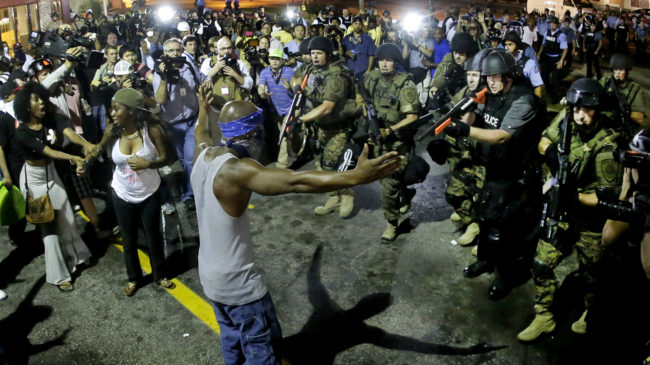 Police arrest a man as they disperse a protest Wednesday for Michael Brown, who was killed by police Aug. 9 in Ferguson, Mo. Charlie Riedel/AP