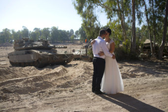 An Israeli couple, Noga and Moshiko Siho, kiss after they have their wedding photos taken Wednesday in an army staging area on the Israel-Gaza border, near Kibbutz Yad Mordechai, Israel. Oded Balilty/AP
