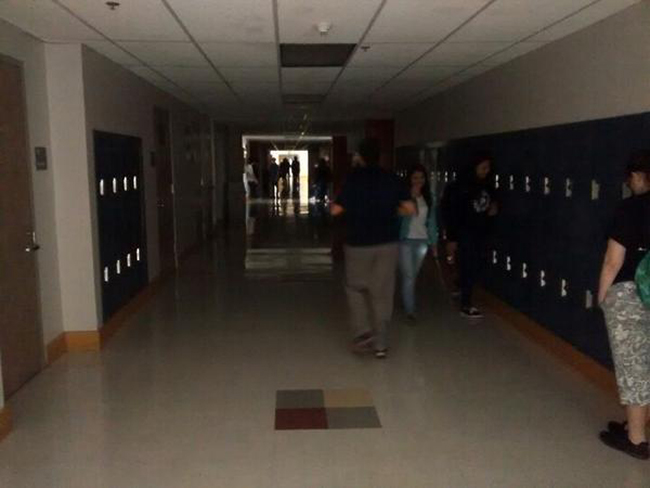 Students stand in a dark hallway at the Juneau-Douglas High School during the power outage this morning. (Photo by Mikko Wilson)