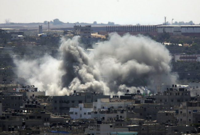 Smoke rises over Gaza City on Friday as Israel and Gaza militants resumed cross-border attacks after a three-day truce expired. Lefteris Pitarakis/AP