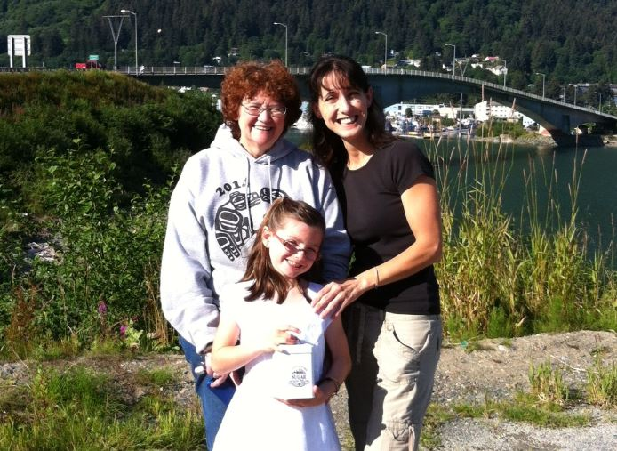 Sheila Short, mother of Amber Schneider, accepted the money from Ildi and Sophia Nylen on Saturday. Sophia, Juneau's youngest busker, gave the $1,562 in cash and two gift certificates in a cookie jar. (Photo courtesy of Ildi Nylen)