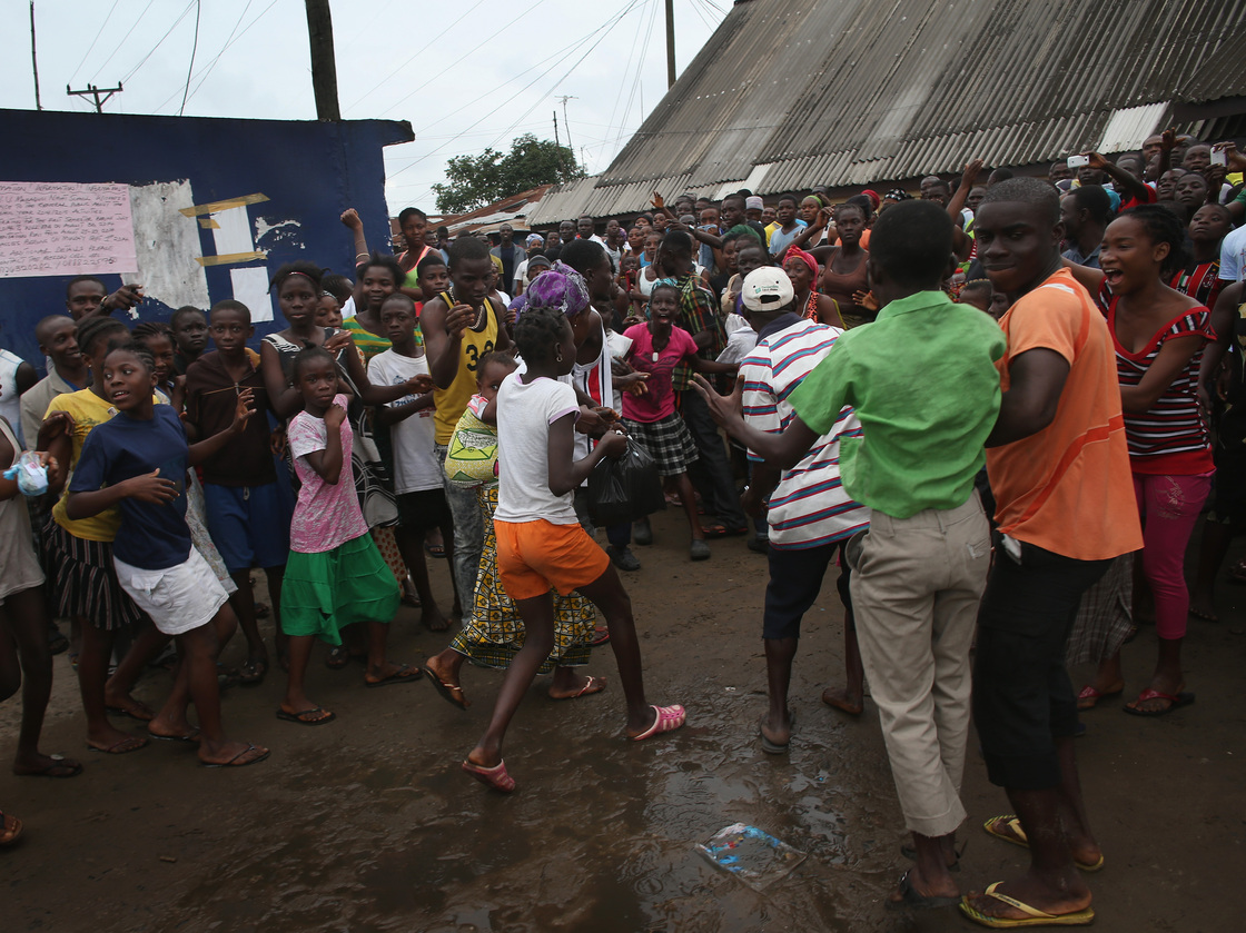 A family (center) leaves an Ebola isolation center after a mob forced open the gates of the facility in the West Point slum on Saturday in Monrovia, Liberia. John Moore/Getty Images