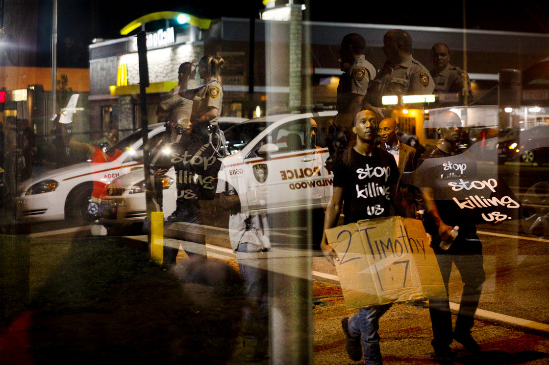 Law enforcement officers are reflected in a window as demonstrators walk past a bus stop in Ferguson. Eric Kayne for NPR