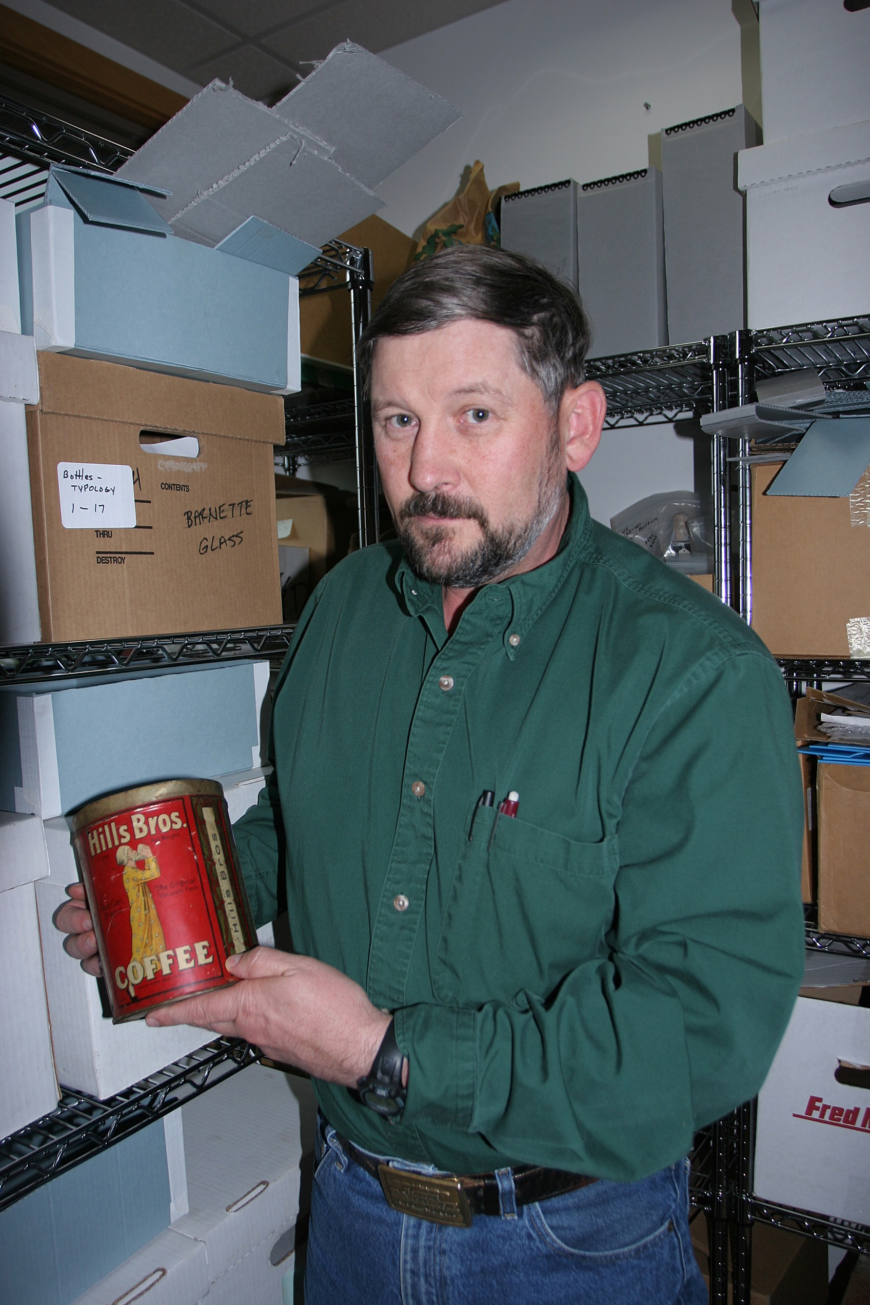 BLM archaeologist Steve Lanford with a Hills Bros. coffee can. (Photo by Craig McCaa/BLM)