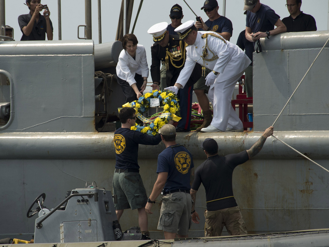 Deputy Chief of Mission (Jakarta, Indonesia) Kristen Bauer (top left), Capt. Richard Stacpoole (top right), and Marine Lt. Col. Miguel Avila pass a wreath to sailors, assigned to Mobile Diving Salvage Unit One, during a wreath-laying ceremony for the sunken Navy vessel USS Houston. Mass Communication Specialist 3rd Class Christian Senyk/U.S. Navy